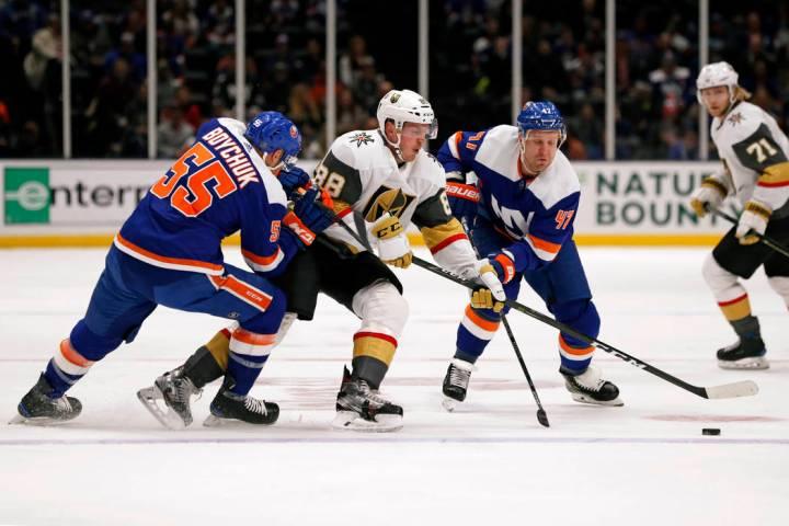 El defensa de los Islanders, Johnny Boychuk (55), y el ala derecha, Leo Komarov (47), rodean al ...