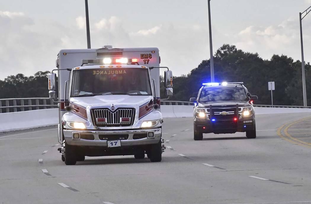 Coches de policía escoltan a una ambulancia después de que un tirador abriera fuego dentro de ...