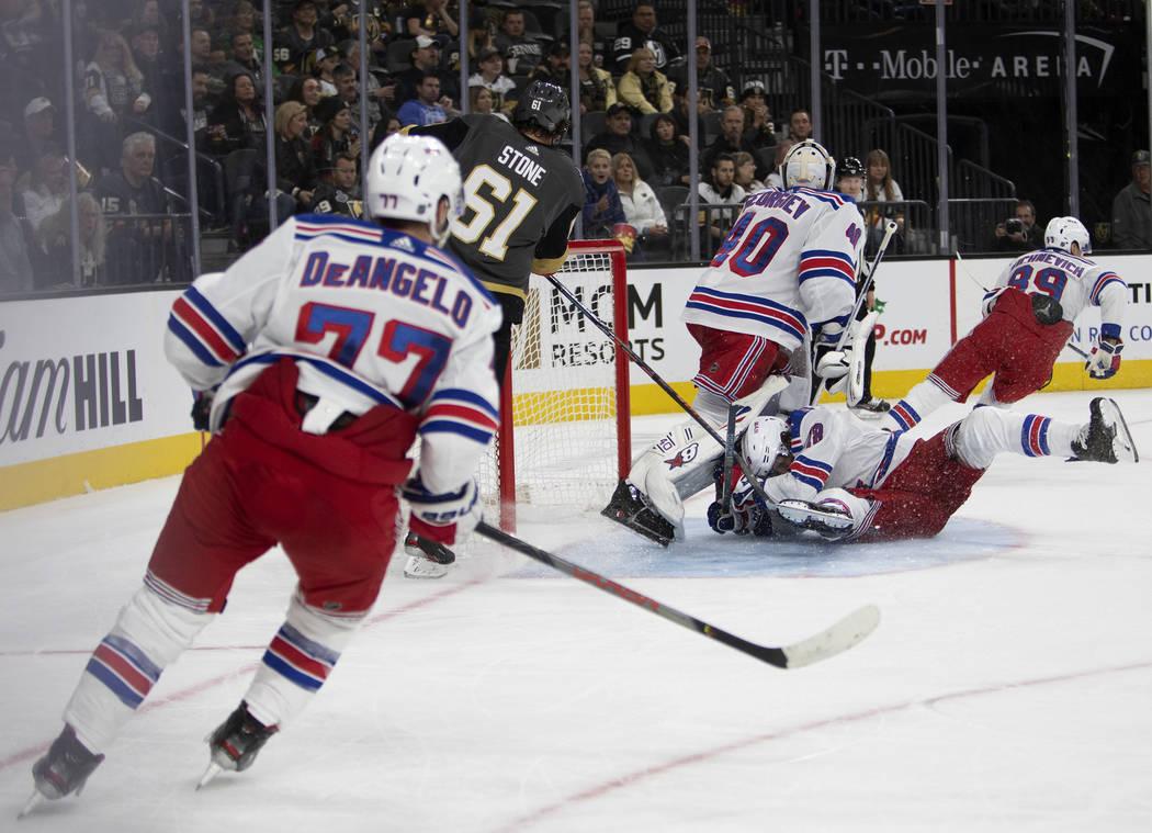 El defensa de los New York Rangers, Jacob Trouba (8), se desliza hacia el portero de los New Yo ...