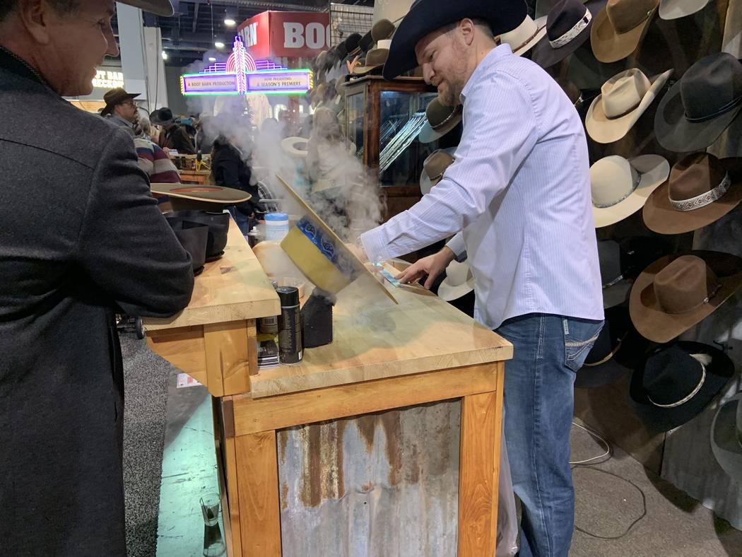 El fabricante de sombreros personalizados, Braydan Shaw, ejerce su oficio mientras el cliente, ...