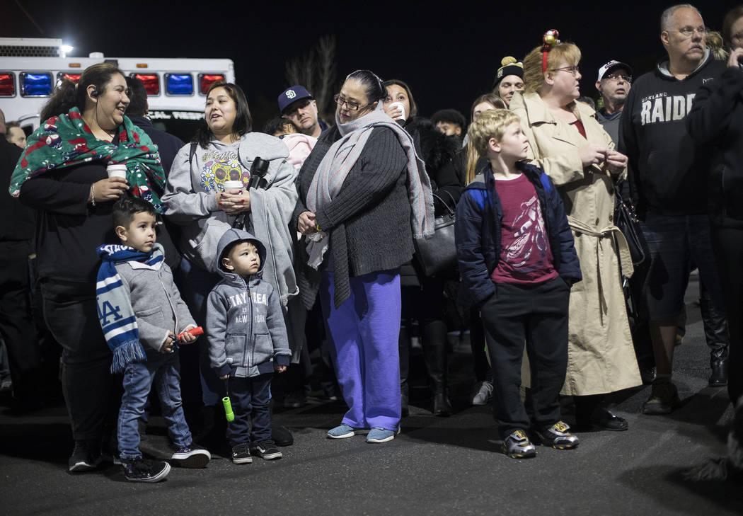 Una multitud espera en el estacionamiento para iluminar con linternas a los niños que están i ...