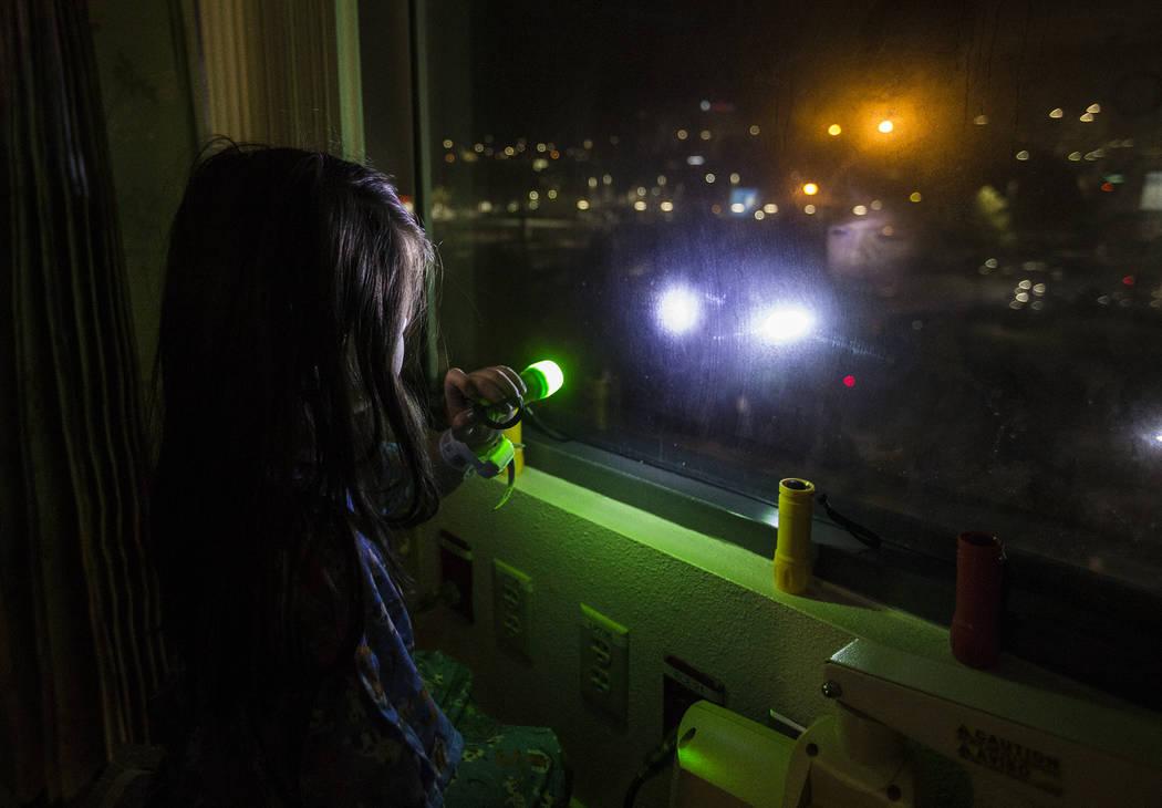 Alicia Langoria-Buffington, de cinco años de edad, enciende una linterna hacia una multitud de ...