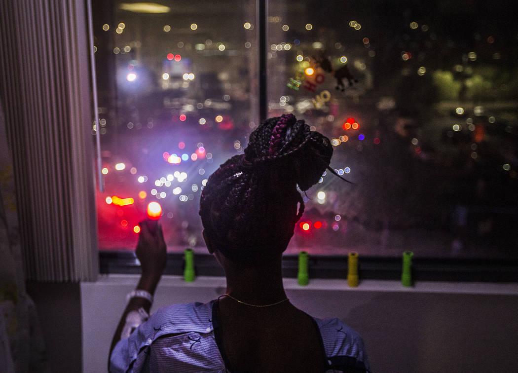 Zion Green, de 12 años de edad, ilumina con una linterna a una multitud de personas en el esta ...