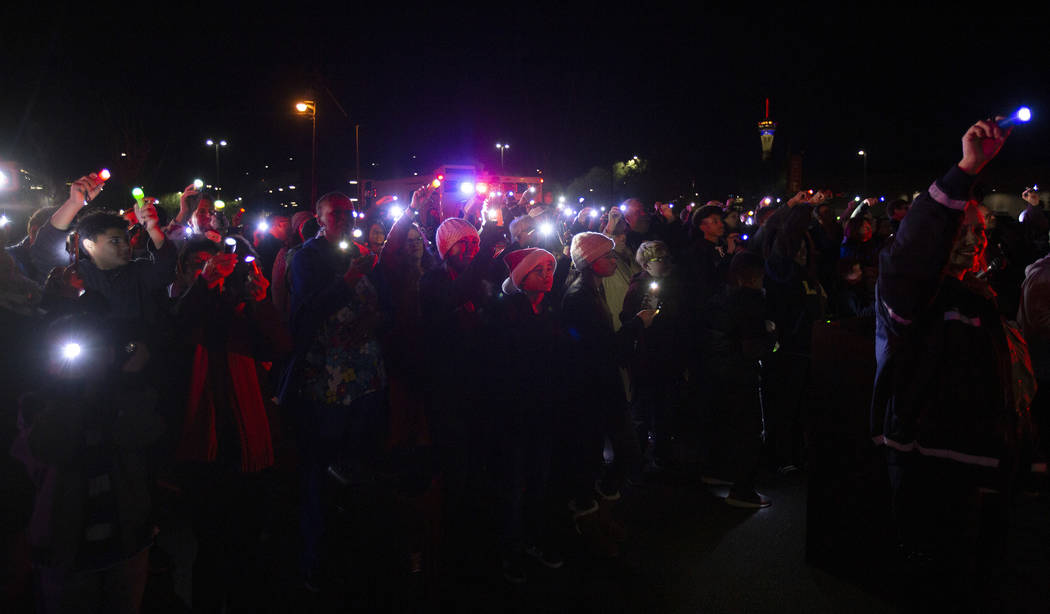 Un grupo de miembros de la comunidad y de los equipos de emergencia iluminan el tercer piso del ...