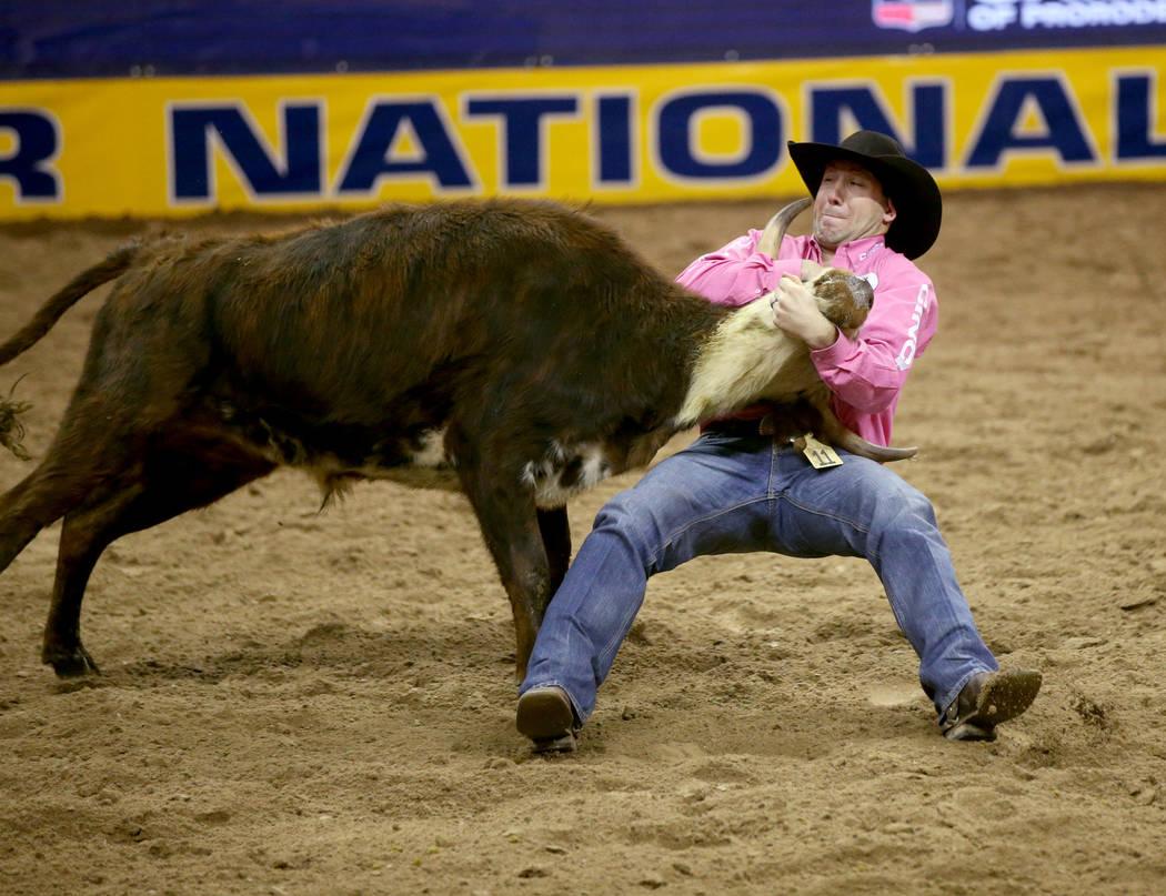 Scott Guenthner de Canadá compite en la lucha de terneros durante la quinta ronda de la NFR Wr ...