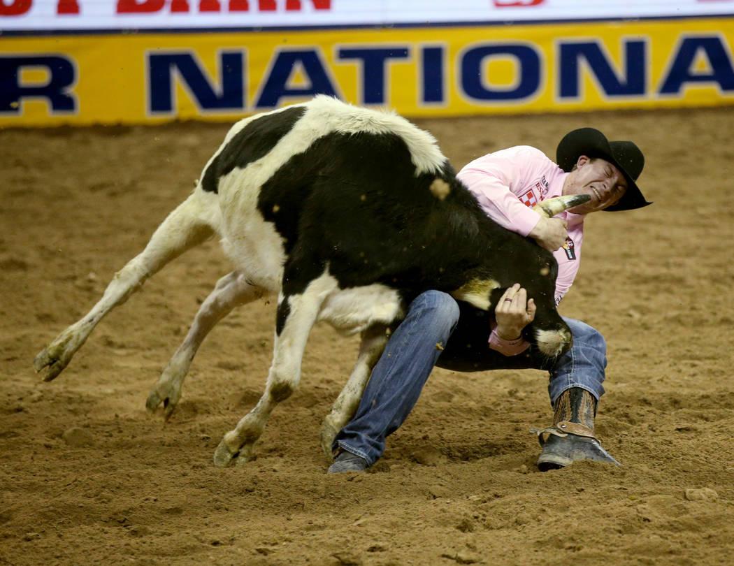 Ty Erickson de Helena, Mont., compite en la lucha de terneros durante la quinta ronda de la NFR ...
