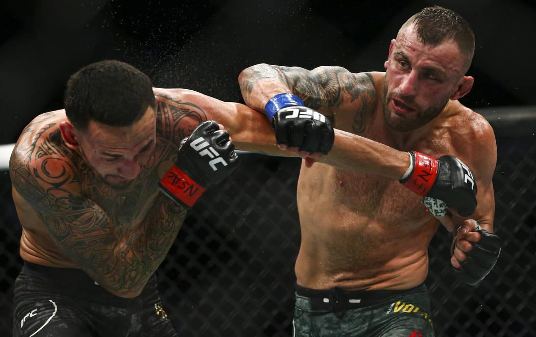 Max Holloway, izquierda, pelea contra Alexander Volkanovski durante su pelea por el título de ...
