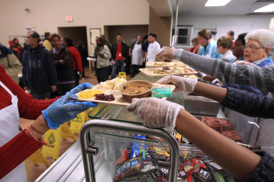 Voluntarios sirven bandejas de pavo durante la comida de Navidad en Las Vegas Rescue Mission el ...