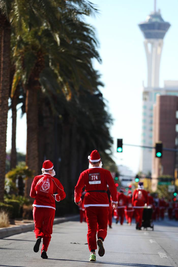 La gente corre en el 14º Great Santa Run anual de Las Vegas en el centro de Las Vegas el sába ...