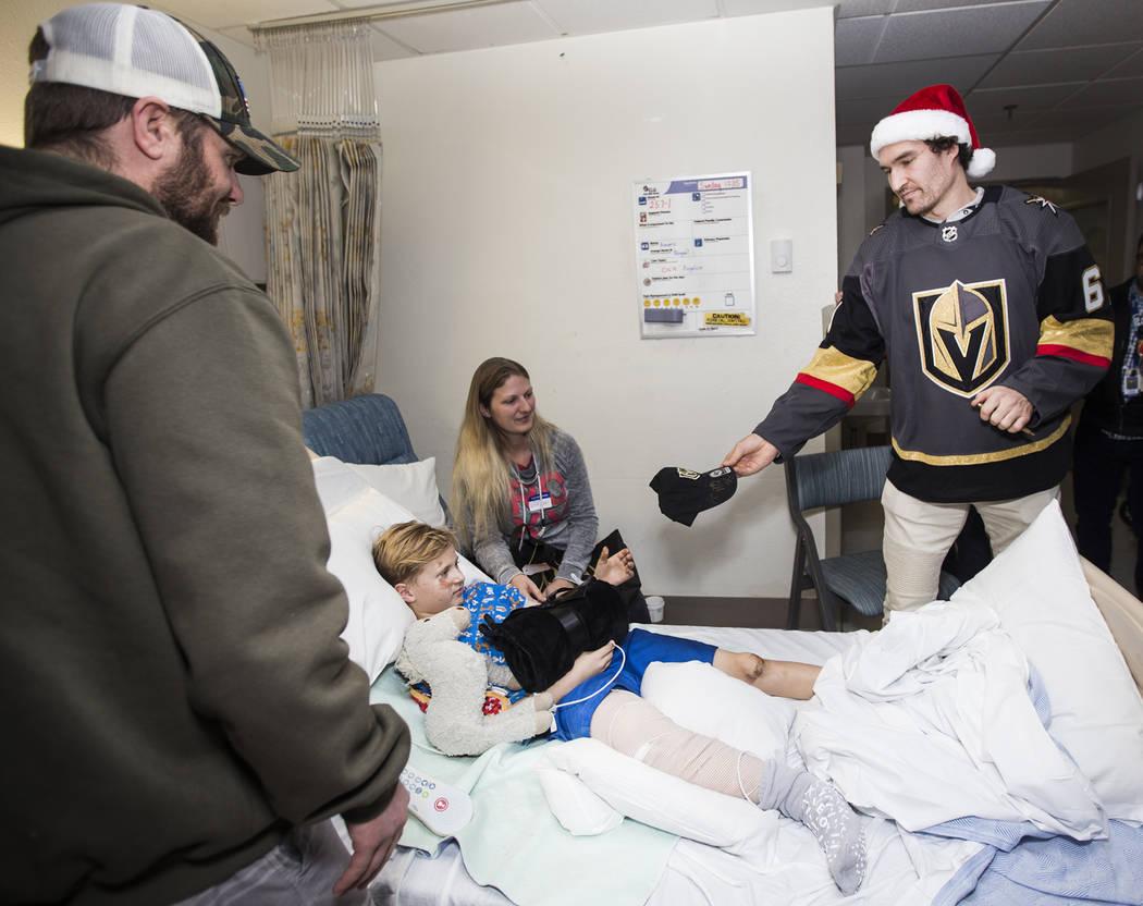 El jugador de los Knights, Mark Stone, le entrega un sombrero firmado a Xavier Lee, de 9 años, ...