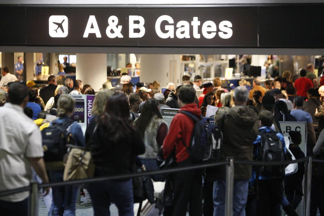 Pasajeros esperan en fila para pasar la seguridad en la Terminal 1 del Aeropuerto Internacional ...