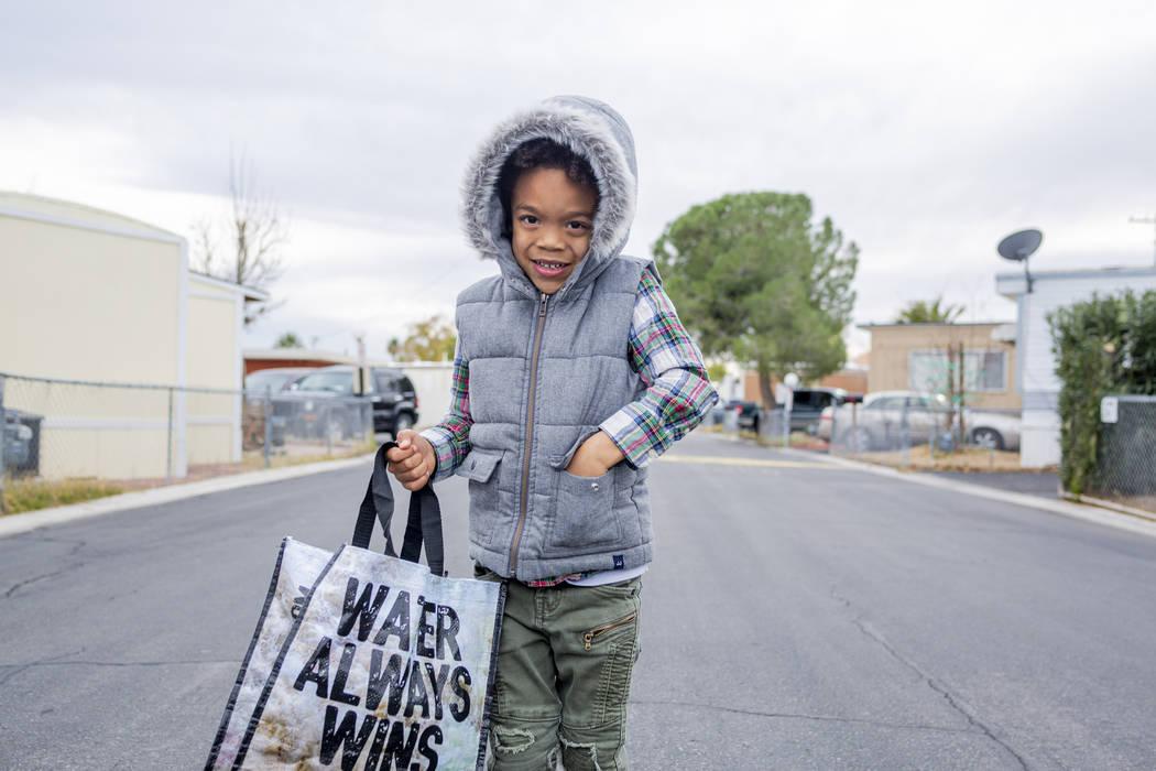 Olamide Ajayi, de 6 años, sostiene un regalo sorpresa de mil dólares recaudados para su maest ...