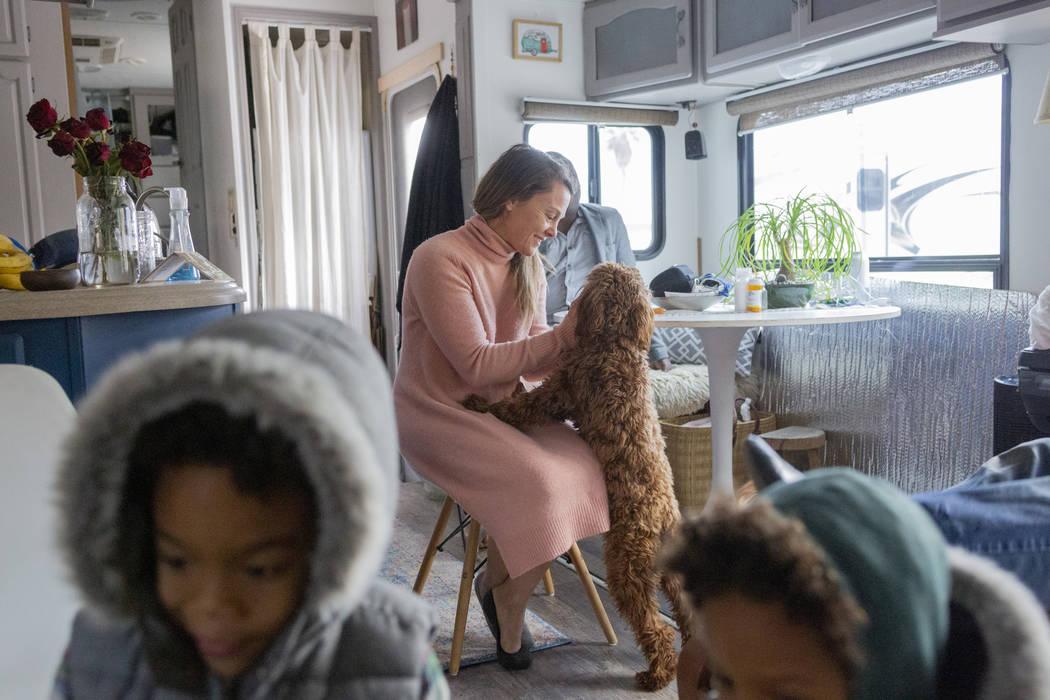 Jill Ajayi, centro, acaricia a Nalulani, la perra de terapia de Lisa Bernauer, en la casa de Be ...