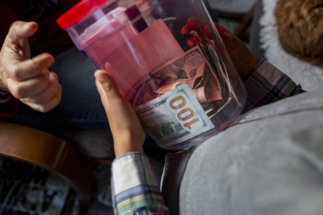 Olamide Ajayi, de 6 años, le muestra a su maestra Lisa Bernauer su regalo de mil dólares, a l ...