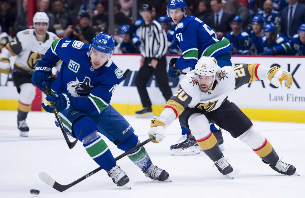 El ala izquierda de los Canucks de Vancouver, Tanner Pearson (70), compite por el control del p ...