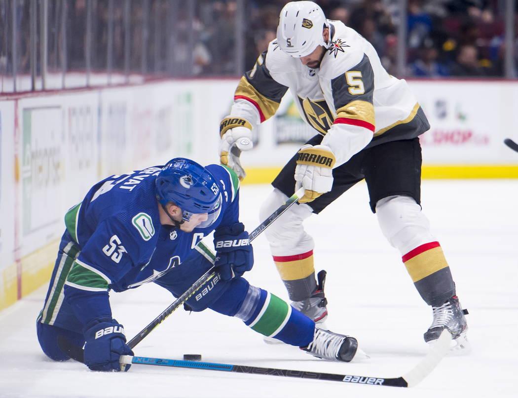 El centro de los Canucks de Vancouver Bo Horvat (53) lucha por el control del puck contra el de ...