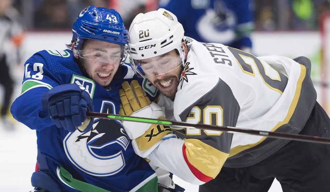 El defensor de los Vancouver Canucks, Quinn Hughes (43), compite por el control del puck contra ...
