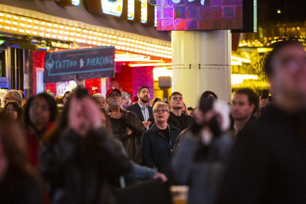 La gente camina debajo de la pantalla recientemente actualizada de Viva Vision mientras un vide ...