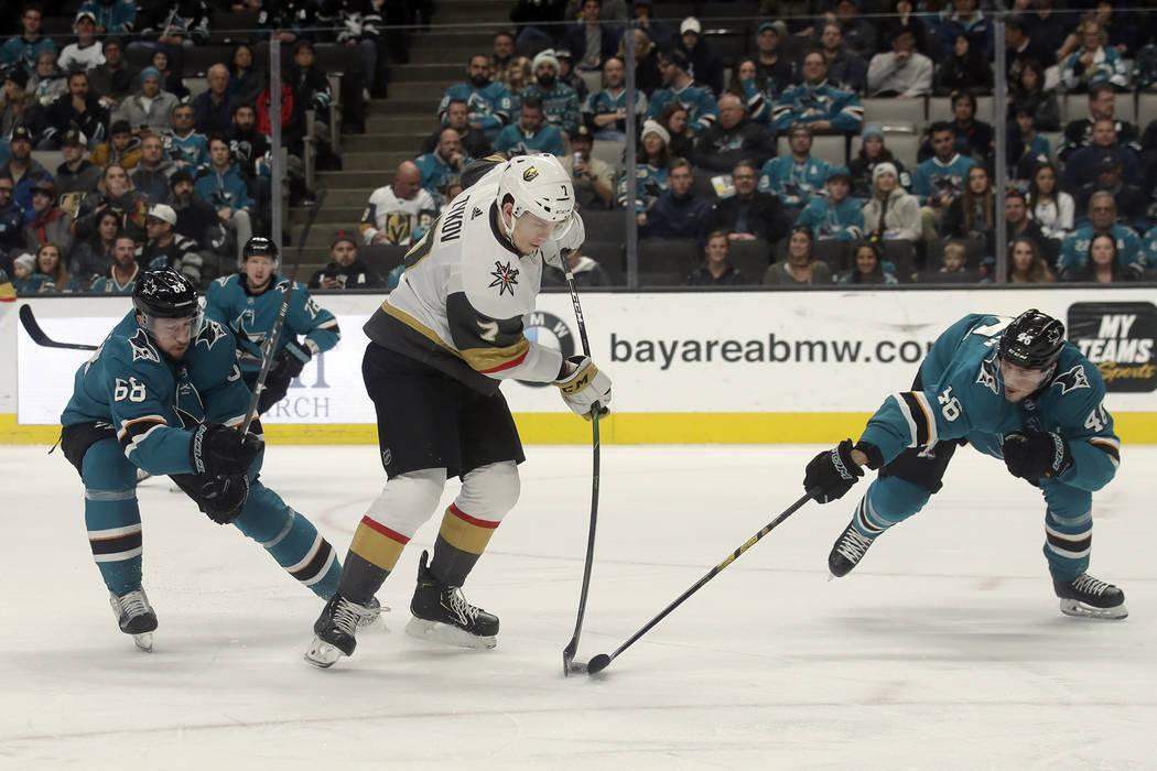 Valentin Zykov, de los Golden Knights de Las Vegas, centro, golpea el puck entre el centro de l ...