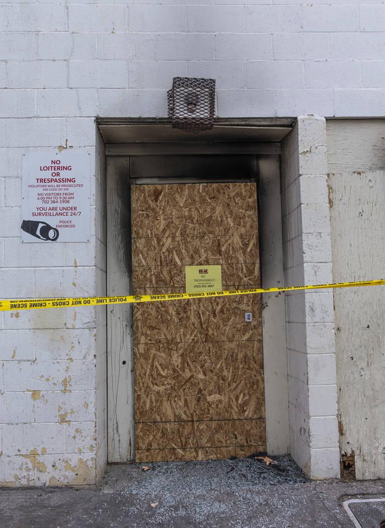 La puerta trasera de cristal rota de los apartamentos del Motel Alpine está tapiada y forrada ...