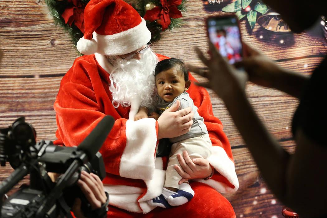 Alijah Hinson toma una foto de su hijo, Anthony Velázquez, de cinco meses de edad, con Papá N ...