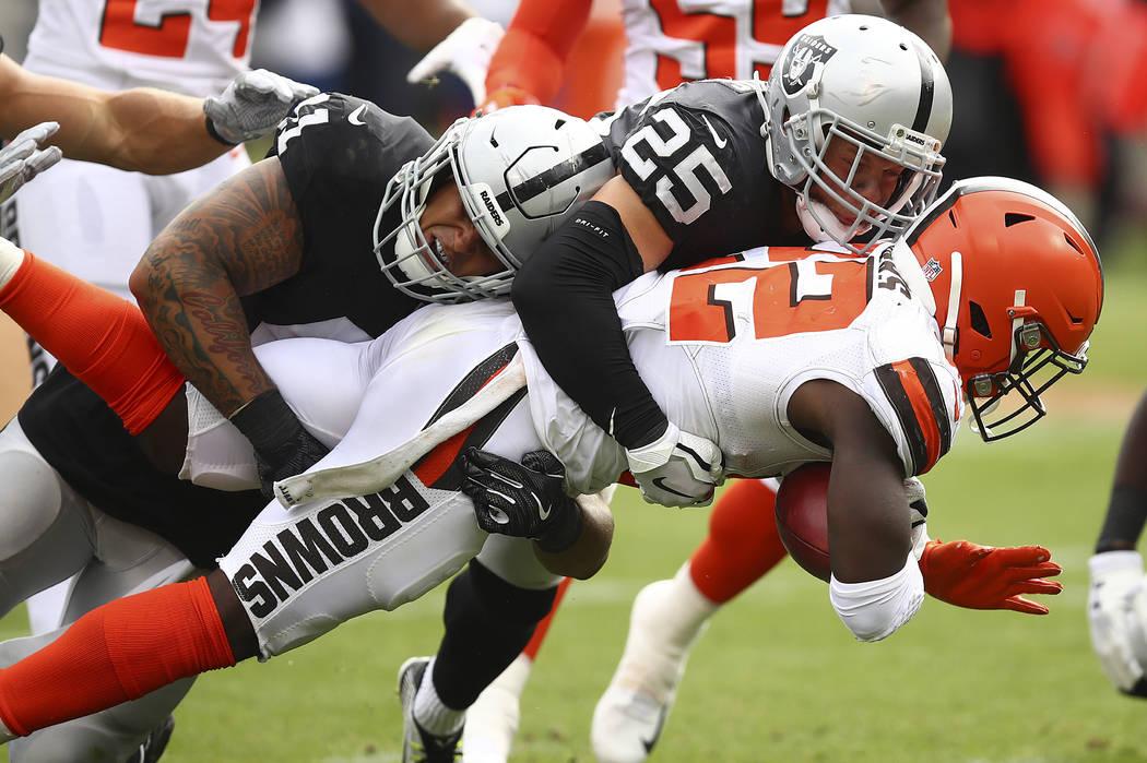 Jabrill Peppers de los Browns de Cleveland, a la derecha, es tacleado por Erik Harris (25) y Ke ...