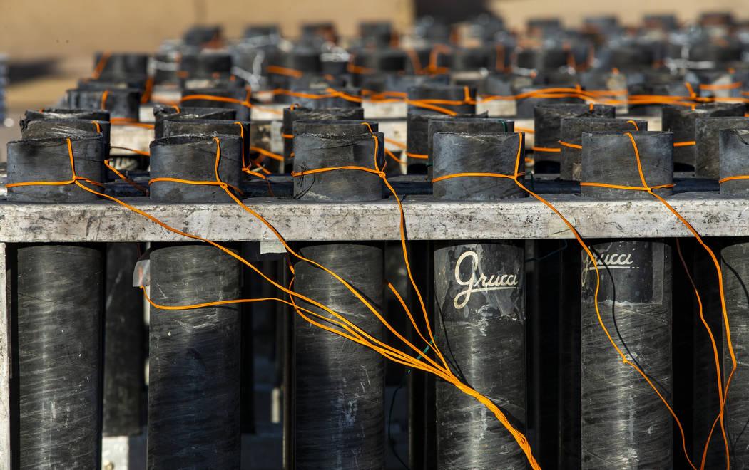 Los morteros se cargan, se conectan y se preparan mientras un equipo de Fireworks by Grucci con ...