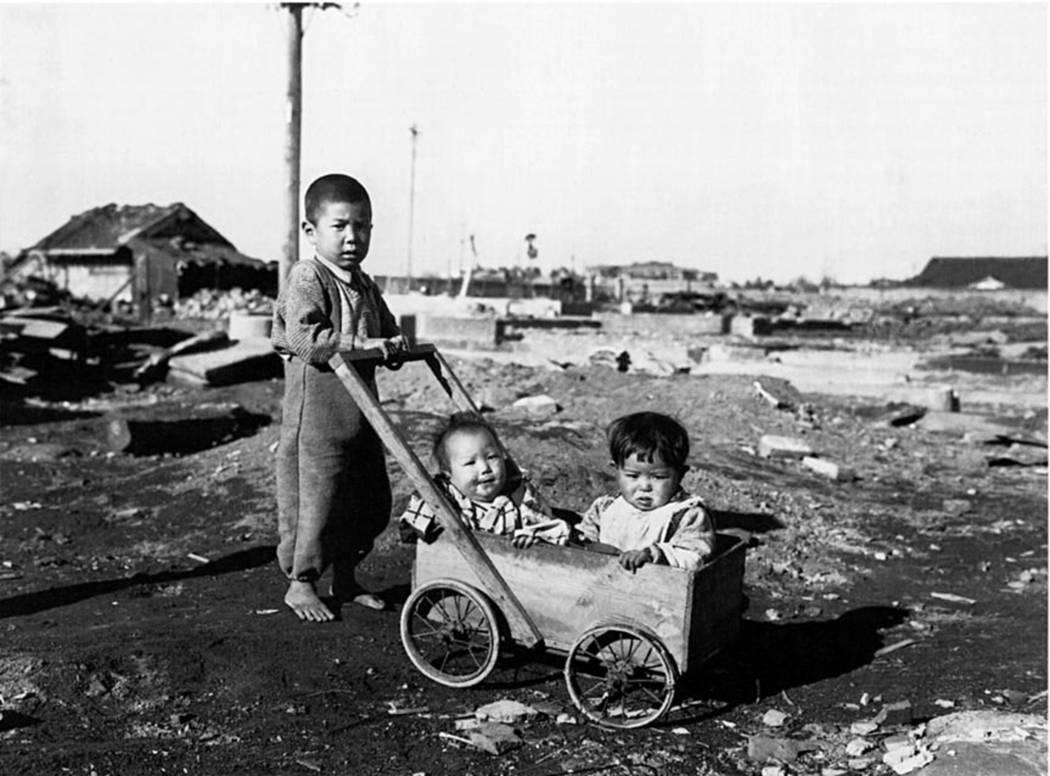 Un niño japonés empuja a dos niños más pequeños en un carrito en esta fotografía tomada e ...