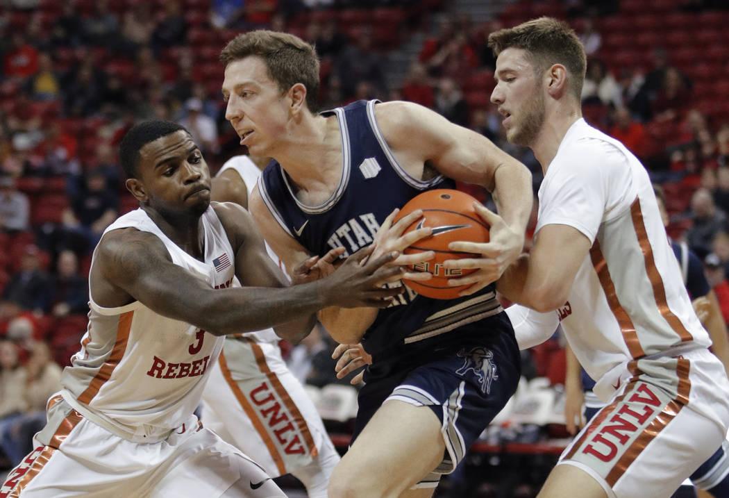 Justin Bean de Utah State, al centro, le quita el balón a Amauri Hardy de la UNLV, a la izquie ...