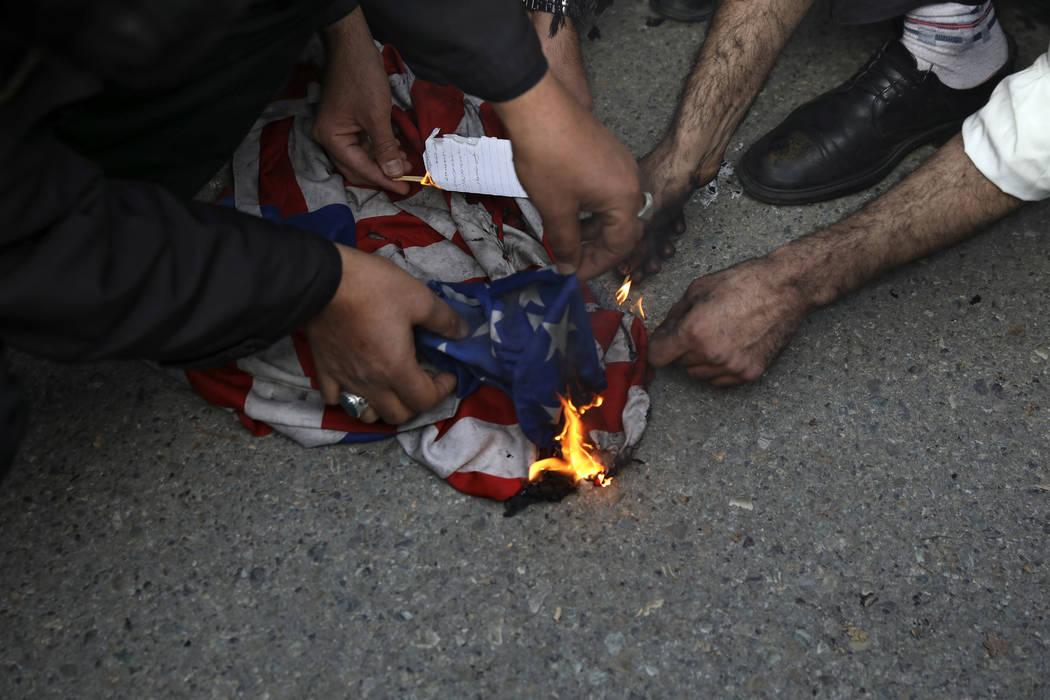 Manifestantes queman una bandera estadounidense durante una manifestación por el ataque aéreo ...