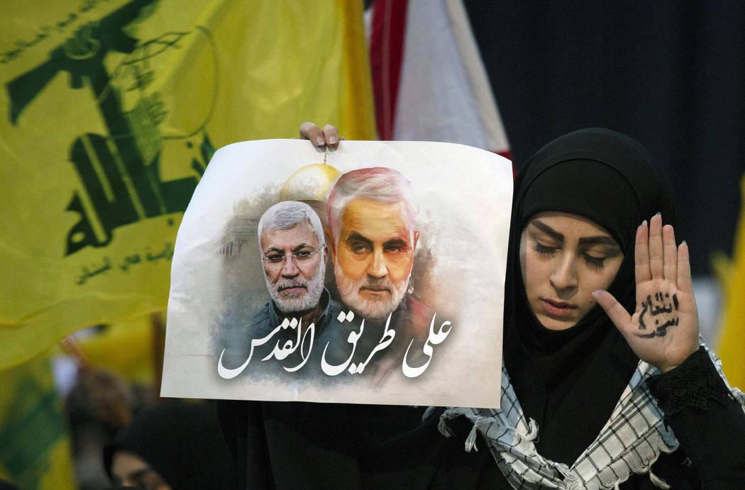 """Una partidaria del líder de Hezbolá, Sayyed Hassan Nasrallah, lleva en la mano las palabras """" ..."""