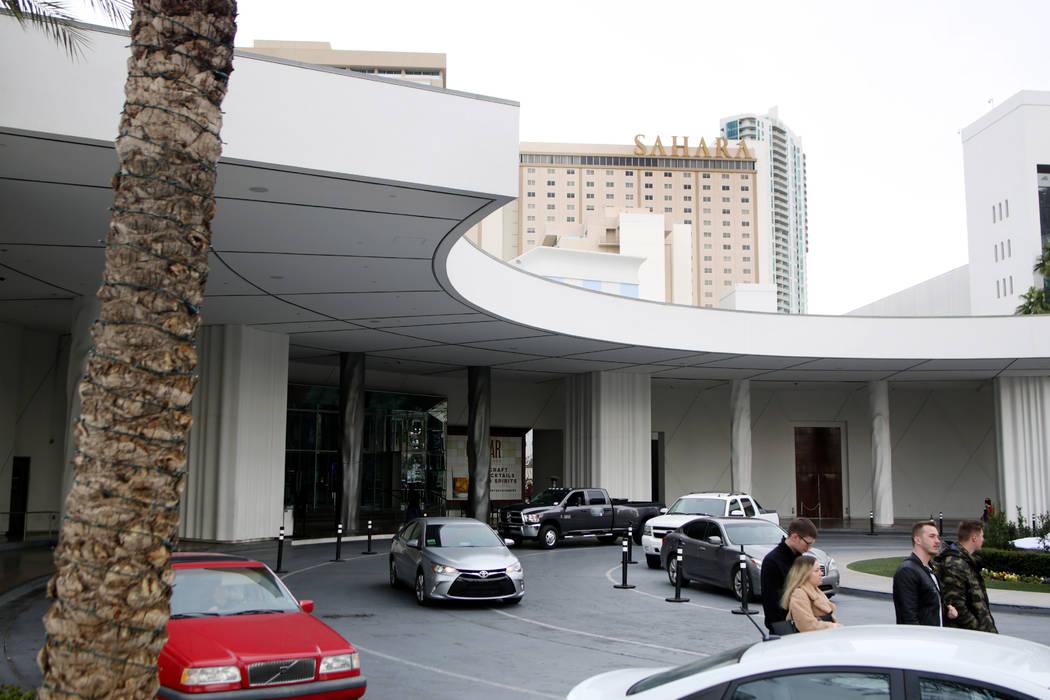 Las personas van y vienen en una entrada donde hay un estacionamiento gratuito disponible en el ...