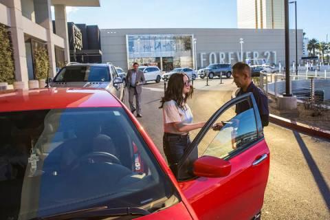 Mark Reolegio, a la derecha, recibe las llaves del auto de Jennifer Sandoval afuera de The Capi ...