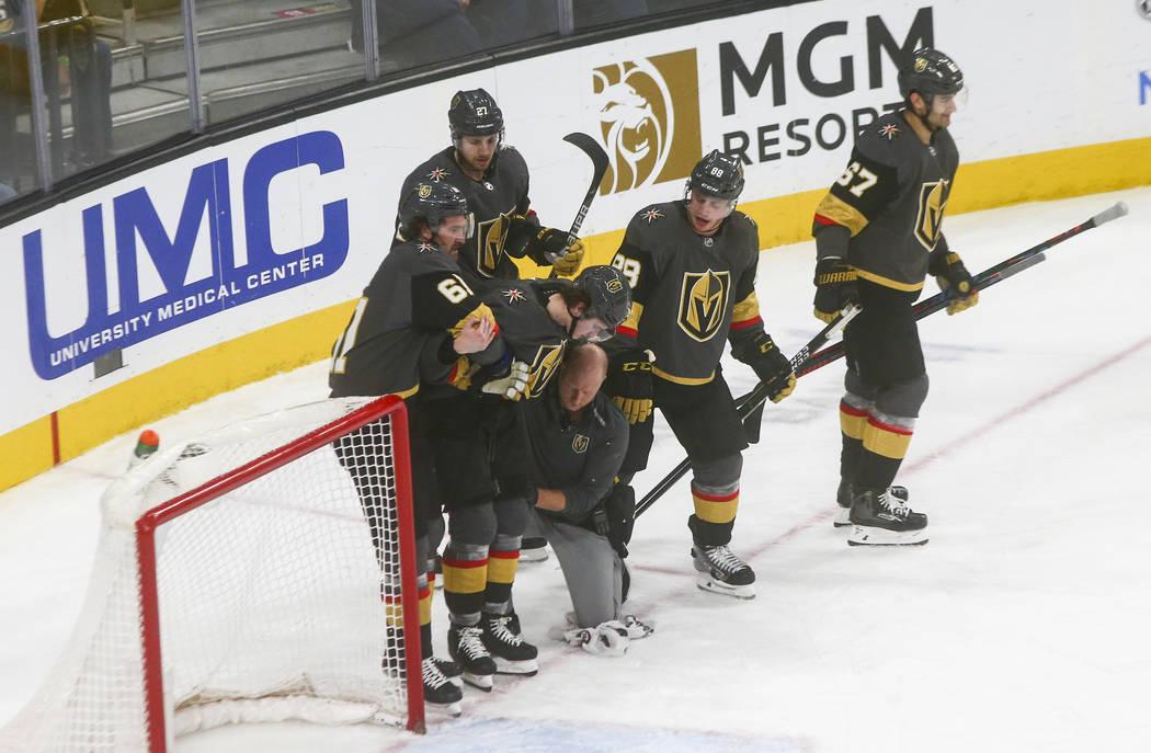 Cody Glass (9) de los Golden Knights es escoltado fuera del hielo con la ayuda de sus compañer ...