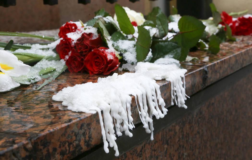 Cera de velas derretidas junto a flores que se colocaron en la Embajada de Canadá durante un d ...