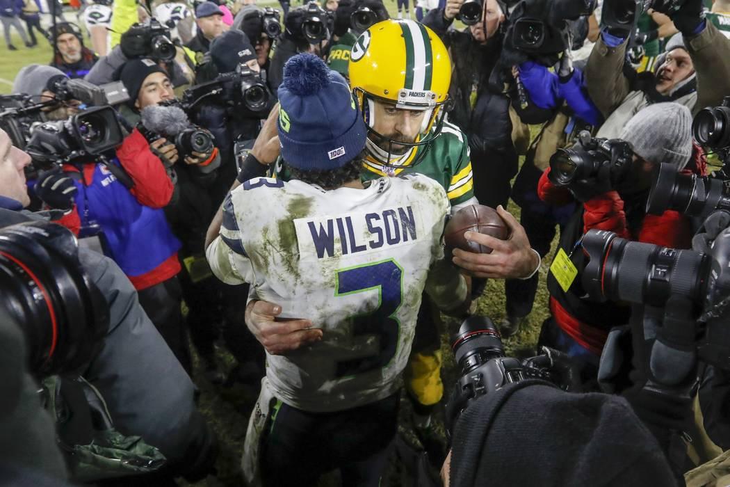 Aaron Rodgers de los Green Bay Packers habla con Russell Wilson de los Seattle Seahawks despué ...