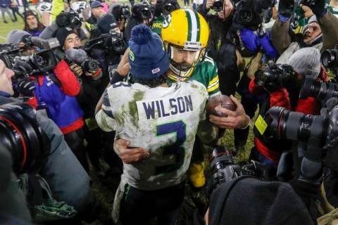 Aaron Rodgers de los Green Bay Packers habla con Russell Wilson de los Seattle Seahawks despué ...