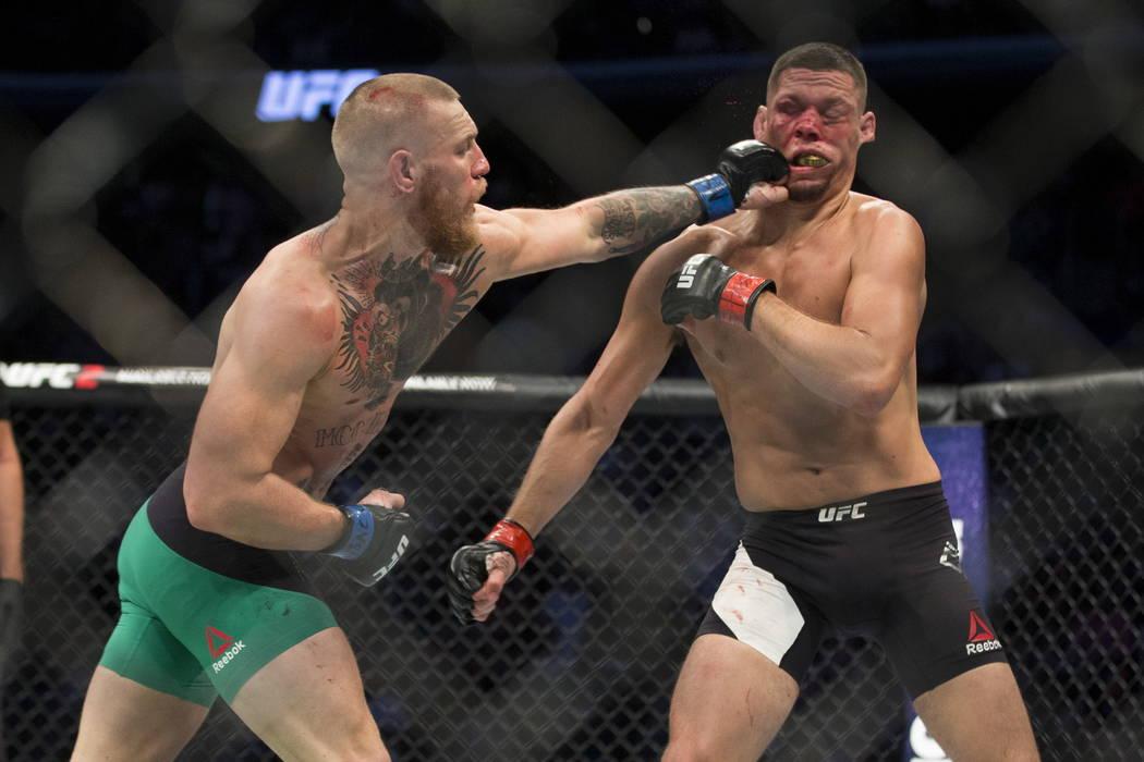 Conor McGregor, izquierda, conecta un golpe de izquierda contra Nate Díaz en el combate de pes ...