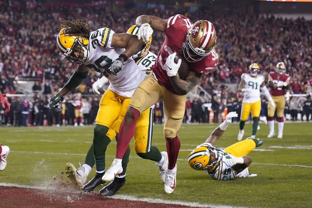 El corredor de los 49ers de San Francisco, Raheem Mostert, centro-derecha, anota un touchdown j ...