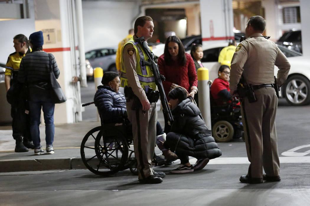 Oficiales de policía armados se paran frente al estacionamiento de Nordstrom en el centro come ...