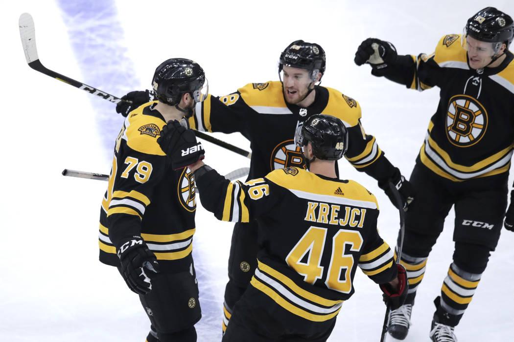 El defensa de los Boston Bruins, Jeremy Lauzon (79), recibe felicitaciones de sus compañeros t ...