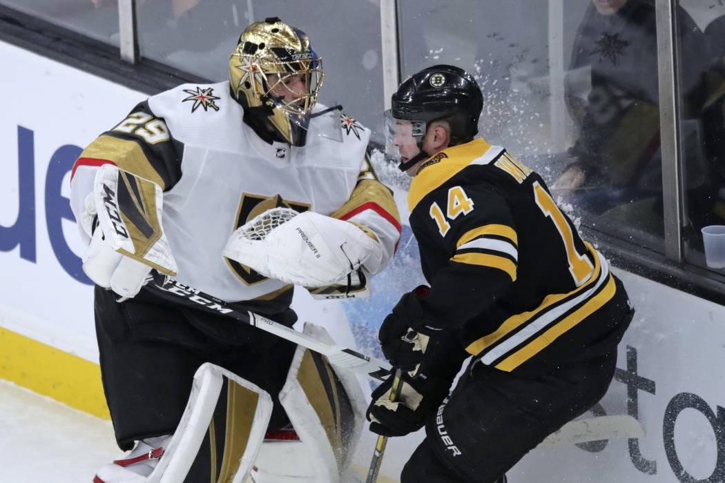 El ala derecha de los Boston Bruins, Chris Wagner (14), se enreda con el portero de los Vegas G ...