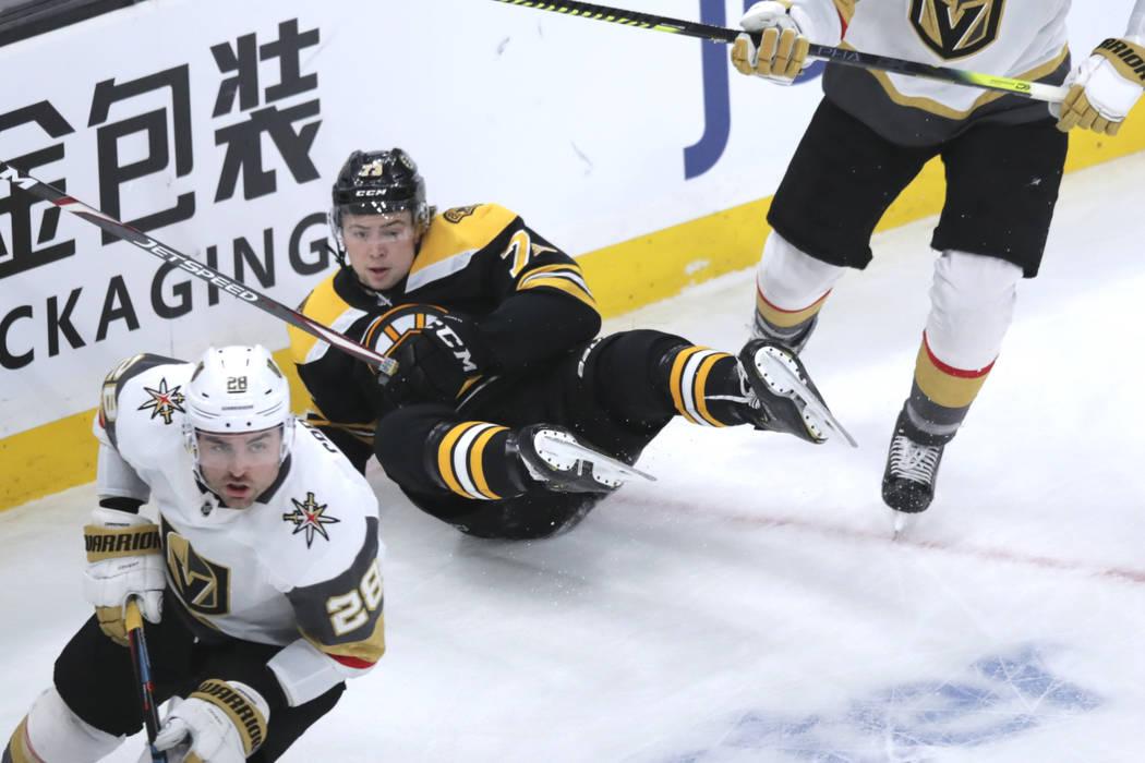 El defensa de los Boston Bruins, Charlie McAvoy (73), cae al hielo durante el primer tiempo de ...