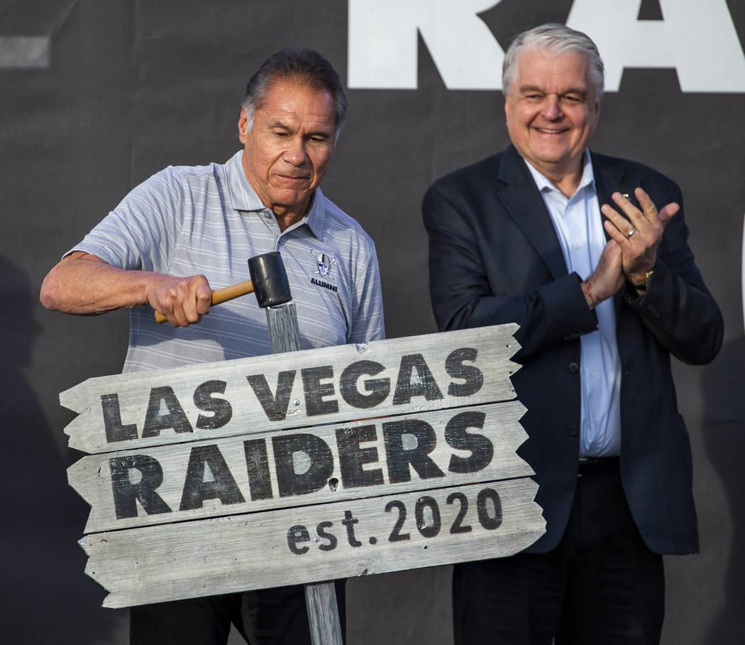 El ex-grande de los Oakland Raiders, Jim Plunkett, izquierda, clava un cartel ceremonial en el ...