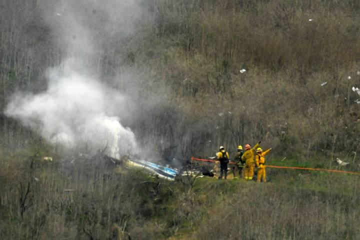 Bomberos trabajan en la escena de un accidente de helicóptero en el que murió la ex estrella ...