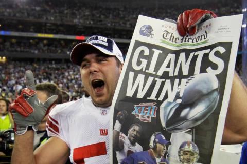 El linebacker de los Giants de Nueva York, Zak DeOssie, sostiene un periódico después de que ...