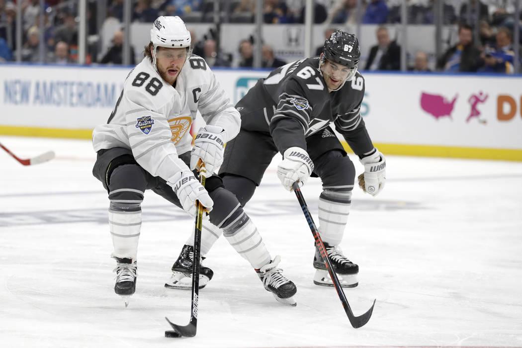 El delantero de los Boston Bruins, David Pastrnak (88), desplaza el puck contra el delantero de ...