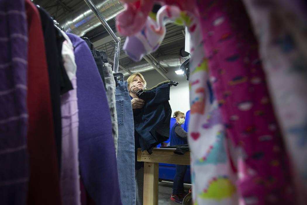 Linda Muth, arriba/izquierda, clasifica la ropa donada en Goodwill del sur de Nevada el miérco ...
