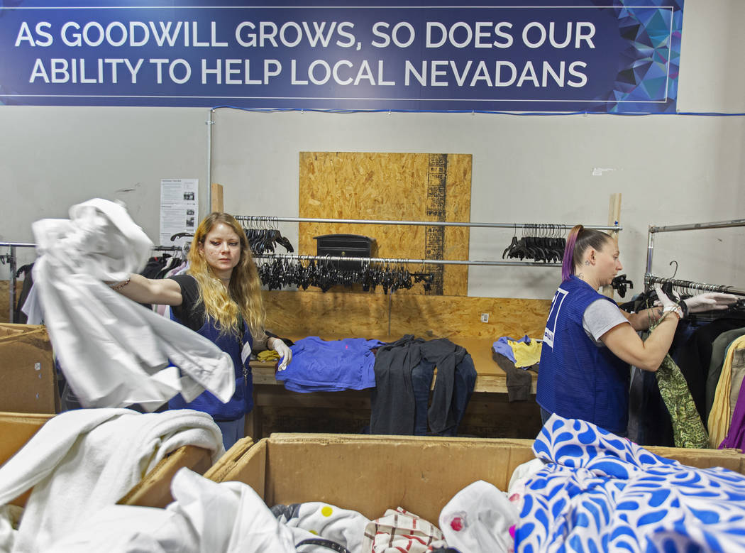 Shawnee Seay, izquierda, y Katie Silber clasifican la ropa donada a Goodwill del Sur de Nevada ...