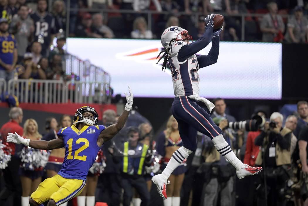 Stephon Gilmore de los New England Patriots, derecha, intercepta un pase destinado a Brandin Co ...